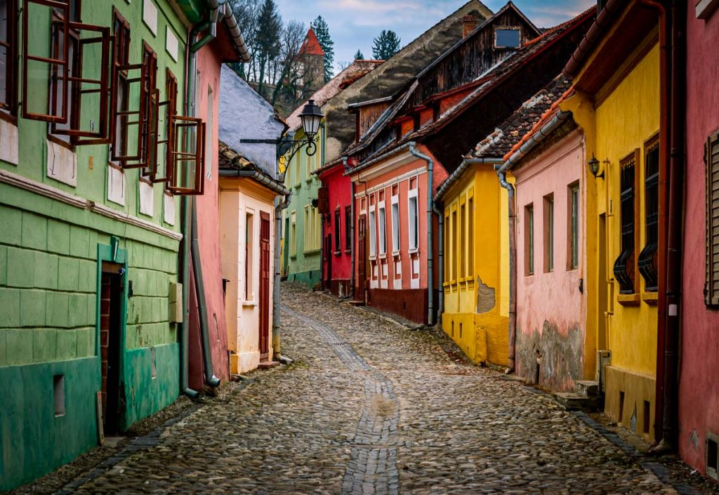 Narrow street with colored houses in Sighisoara with the Church on the Hill in the background on the image.