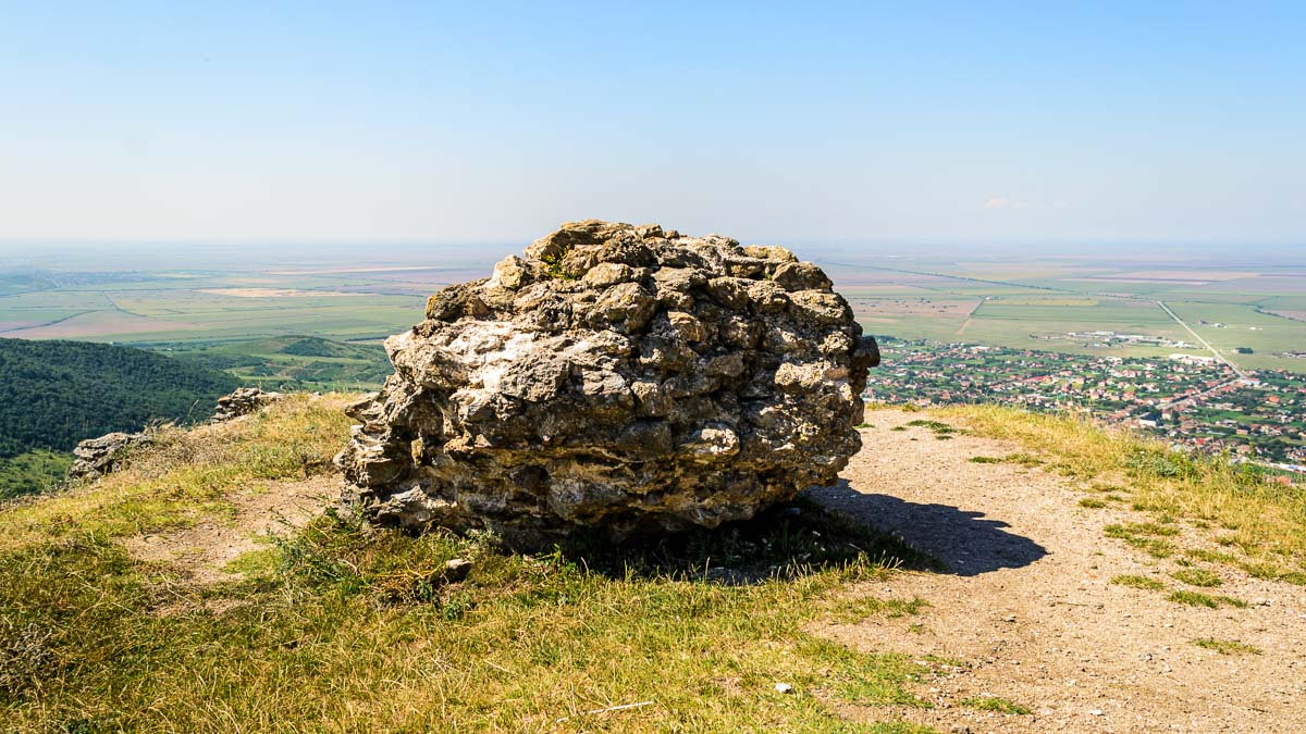 Large round shaped wall part with the commune of Șiria in the background.