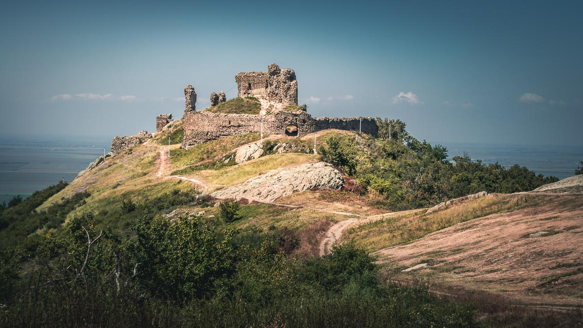 The Șiria fortress on the edge of the hill with a large plain in the background.