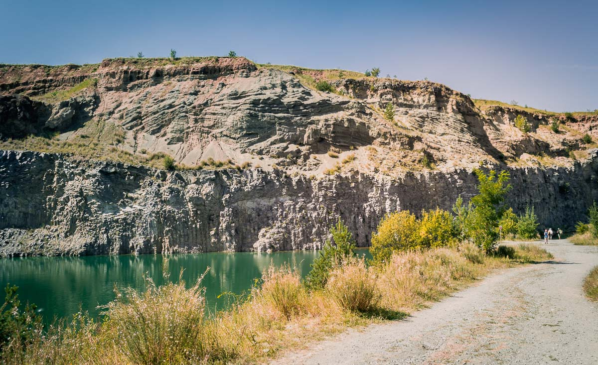 The road inside the former quarry with tourists walking towards the lake.