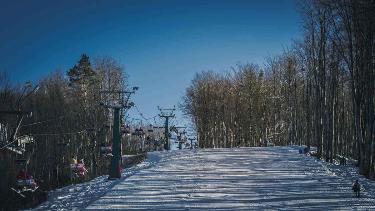 Văliug ski slope in winter with tourists.